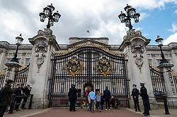 © Licensed to London News Pictures. 09/04/2021. LONDON, UK. Well wishers leave flowers watched by police outside Buckingham Palace after the death of Prince Philip, aged 99, was announced.  Photo credit: Stephen Chung/LNP