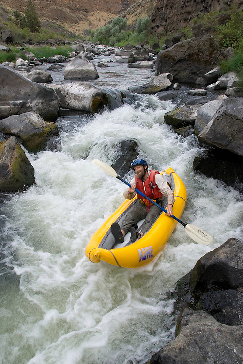 Paddling an inflatable kayak down the rapids of Oregon's Crooked River.