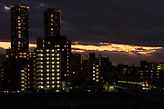 Sunset light behind towering apartment buildings and a commuter train near Musashi Kosugi, Kanagawa, Japan. Thursday January 9th 2020