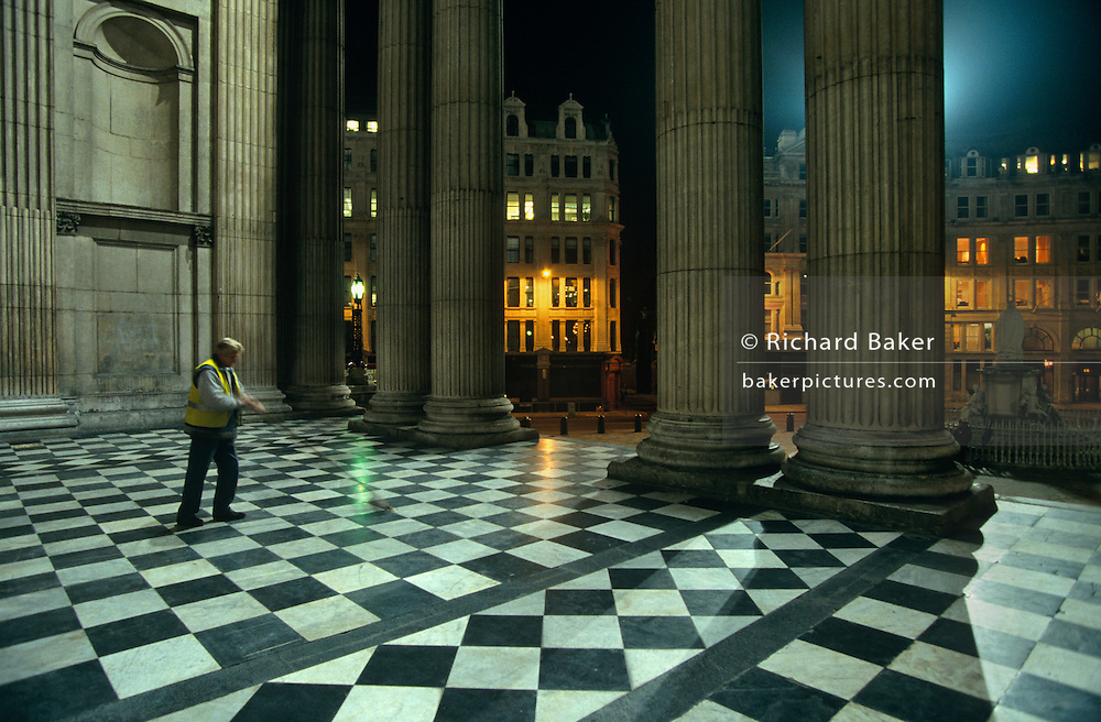 A cleaning contractor sweeps the chequered floor of St. Paul's Cathedral at night in the City of London.
