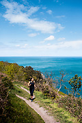 Woman running on the cliff paths and enjoying the view of the ocean at the same time on Jersey's north coast