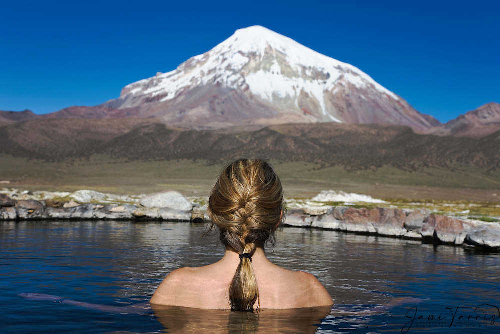 A back view of a  woman sitting in a hot spring in front of volcano Sajama, Parque Nacional Sajama, Bolivia