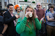 London, UK. Sunday 16th March 2014. Revellers gather in central London for the annual St Patrick's Day celebrations. Saint Patrick's Day or the Feast of Saint Patrick is a cultural and religious holiday celebrated annually on 17 March, the death date of the most commonly-recognised patron saint of Ireland, Saint Patrick. Nowadays the celebration is a fun excuse for some craic and lots of drinking. People encouraged to down their drink in one.