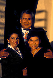 Stock photo of a mother and father with their daughter at her graduation