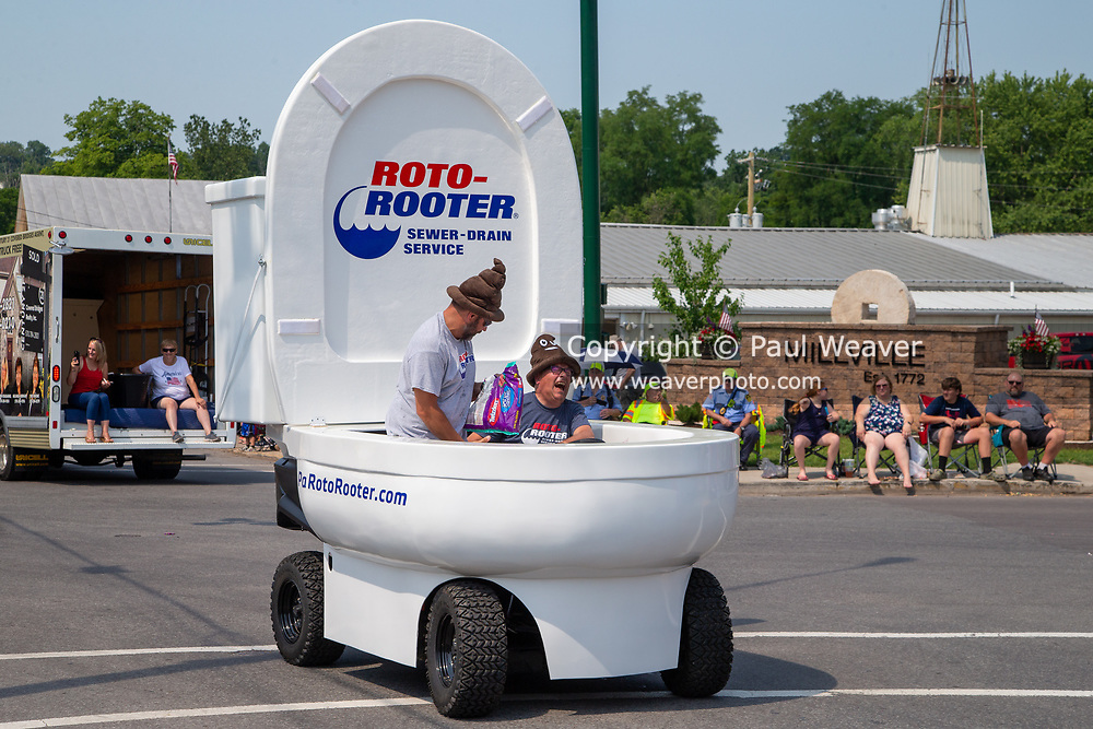 Two men drive a toilet-shaped vehicle sponsored by Roto-Rooter in an Independence Day parade in Millville, Pennsylvania on July 5, 2021.