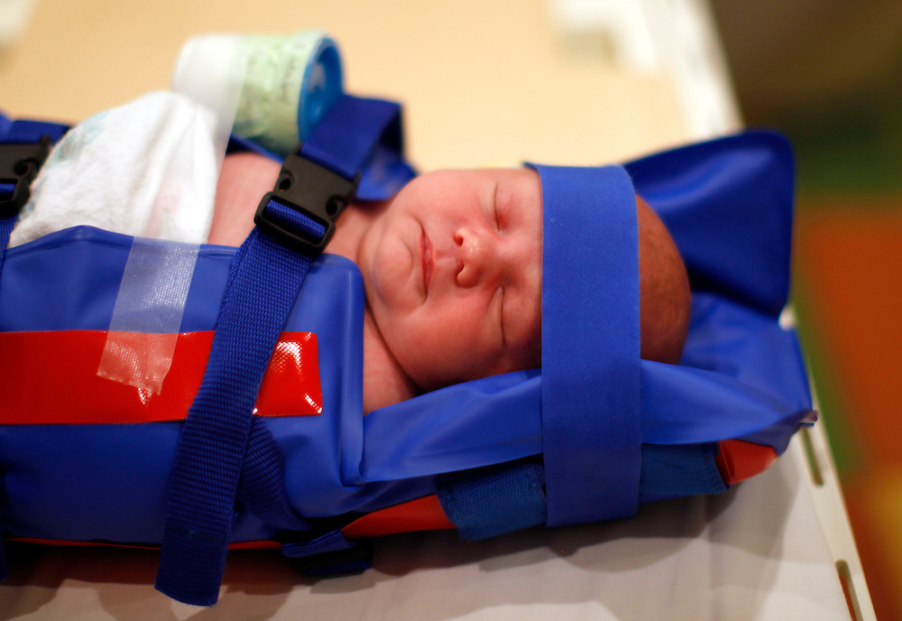 Michael Grabinski, two weeks old sleeps immobilized in an inflatable jacket before going into a MRI machine at The Children's Hospital in Aurora, Colorado August 23, 2010 during a research study on obesity in infants. The overall theme of the study is to understand the continuum of growth that starts really at conception, and to understand if the earliest phases of growth impacts later risk for obesity.    REUTERS/Rick Wilking (UNITED STATES)