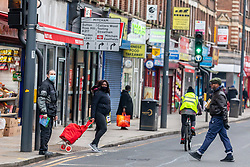 © Licensed to London News Pictures. 01/02/2021. London, UK. Members of the public wearing masks walk through Mitcham Town Centre South London as door to door testing is to be carried out in London and Surrey after two people tested positive for the South African mutation. Today, two people tested positive in Woking, Surrey for the South African Covid-19 variant by community transmission with no links to South Africa as 800,000 people in England and the South East will be offered urgent Covid-19 tests. Photo credit: Alex Lentati/LNP
