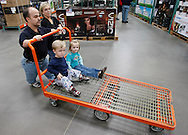 Chris Kotzian (L) pushes a cart on a shopping trip with wife Barb (R) son Adam (lower L) and daughter Avery (lower R) in Thornton, Colorado March 25, 2010.  Chris, Barb and Adam are achondroplasia dwarfs with a rare genetic disorder of bone growth. Avery is average size. Preferring to be called little persons Chris and Barb are active in the Little People of America, the only dwarfism support organization that includes all 200+ forms of dwarfism.  REUTERS/Rick Wilking (UNITED STATES)
