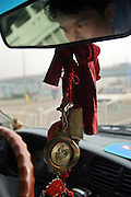 SHAOSHAN, CHINA - 4 NOVEMBER 2005 - A taxi driver has a Mao Zedong souvieners on his rear-view mirror as he drives around Shaoshan. Mao's divine status has brought a great deal of business to Shaoshan. Indeed, it has become the main cottage industry of this small but prosperous town.  Photo by Natalie Behring