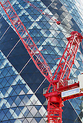 Red HTC crane in front of the Gherkin (St Mary's Axe).<br /> <br /> Architect: Fosters & Partners