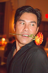 Asian American man with a flower in his mouth at a party