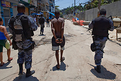 Policiais prendem suposto traficante de drogas durante a incursão na favela do Morro do Alemão em 28 de novembro de 2010 no Rio de Janeiro, Brasil. Após dias de preparação, forças de segurança do Brasil, lançaram um ataque contra uma favela, onde entre 500 e 600 traficantes de drogas estão escondidos e recusam a se render. Cerca de 2.600 tropas aerotransportadas, marines e membros das unidades de elite da polícia participaram da operação como alvo um grupo de favelas sem lei conhecido como Complexo de Alemão. FOTO: Jefferson Bernardes/Preview.com