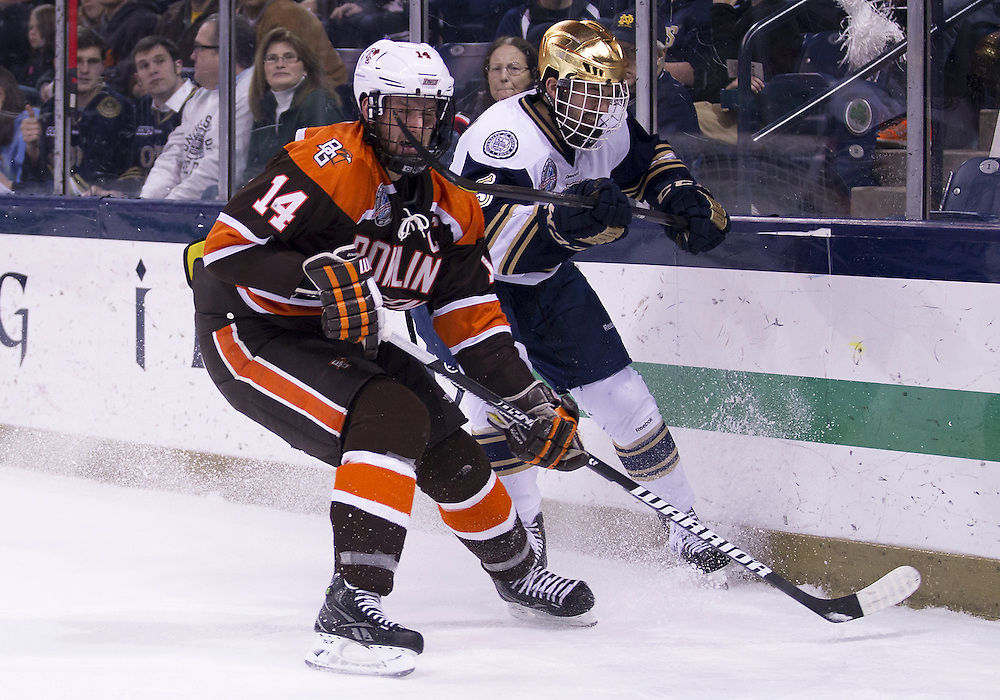 March 15, 2013:  Bowling Green forward Camden Wojtala (14) and Notre Dame defenseman Robbie Russo (5) battle for the puck during NCAA Hockey game action between the Notre Dame Fighting Irish and the Bowling Green Falcons at Compton Family Ice Arena in South Bend, Indiana.  Notre Dame defeated Bowling Green 1-0 in overtime.