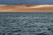 Desert sand dunes at Lac Naila with dark cloudy sky, Morocco.
