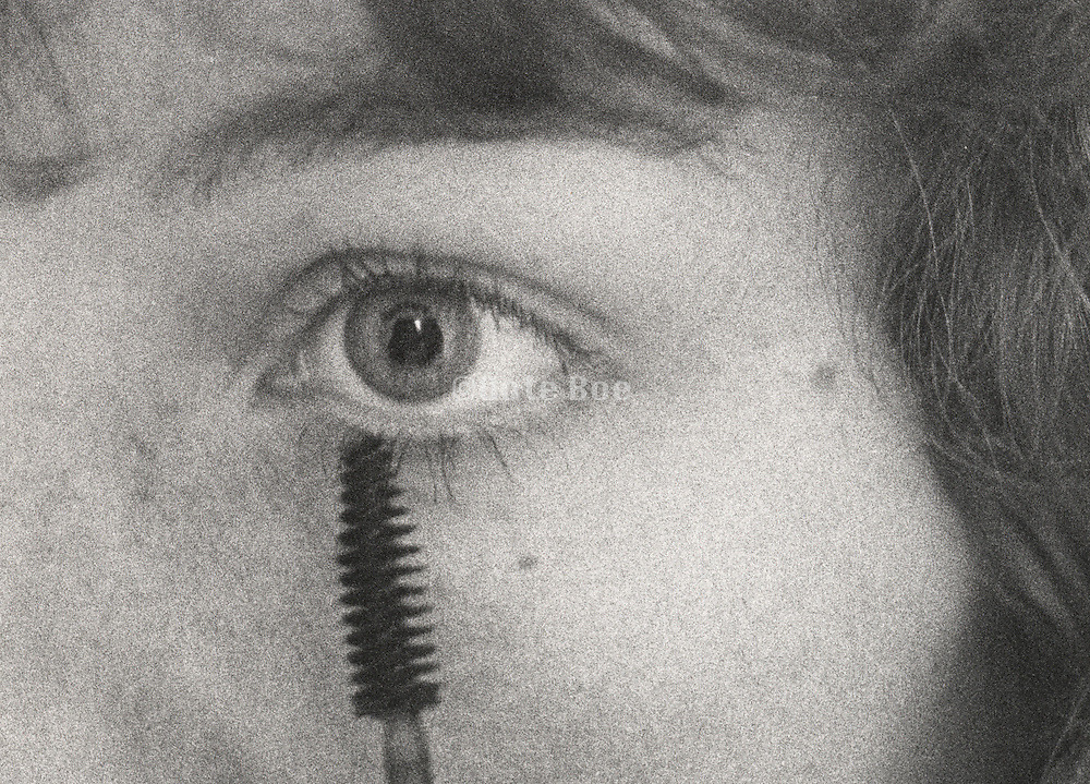 Close up of a woman doing her eyelashes with a mascara brush
