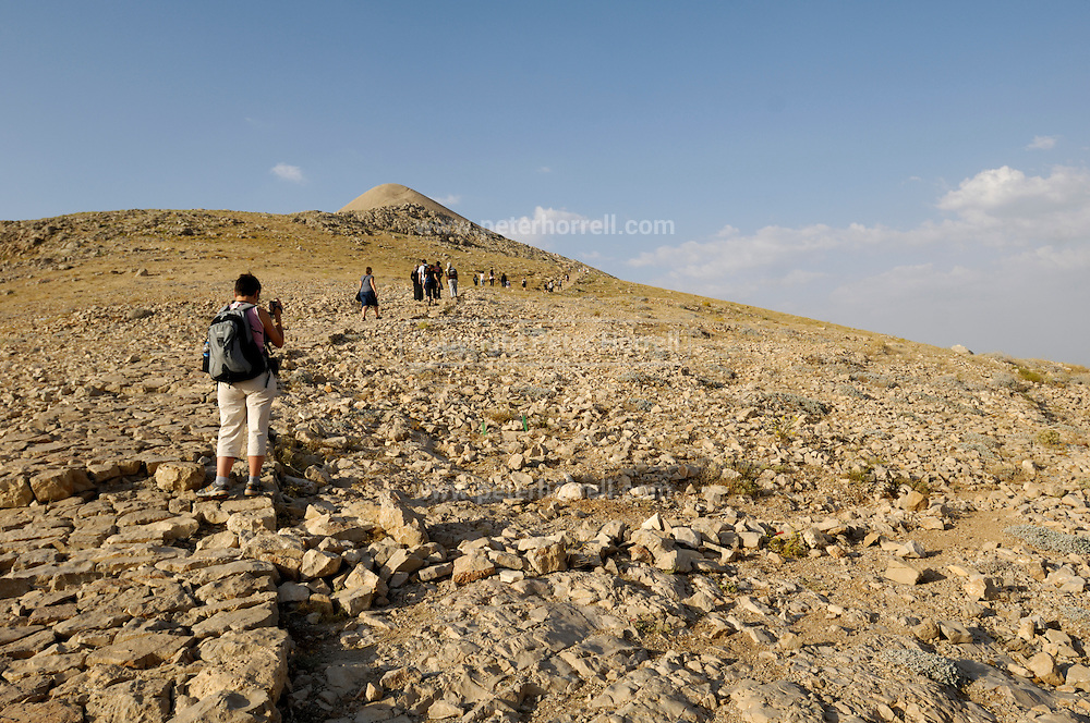 Turkey July 28 2011: Visitors walk to the top of Nemrut Dagi (2,134 m) in time to view the sunset.  Copyright 2011 Peter Horrell