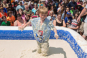 A young boy stands up in a vat of grits during the World Grits Festival rolling in the grits contest April 12, 2014 in St. George, South Carolina. Contestants have to roll in a vat of grits and the one with the most grits sticking to their body wins. Grits are a tradition Southern dish of thick maize-based porridge made from dried corn hominy.