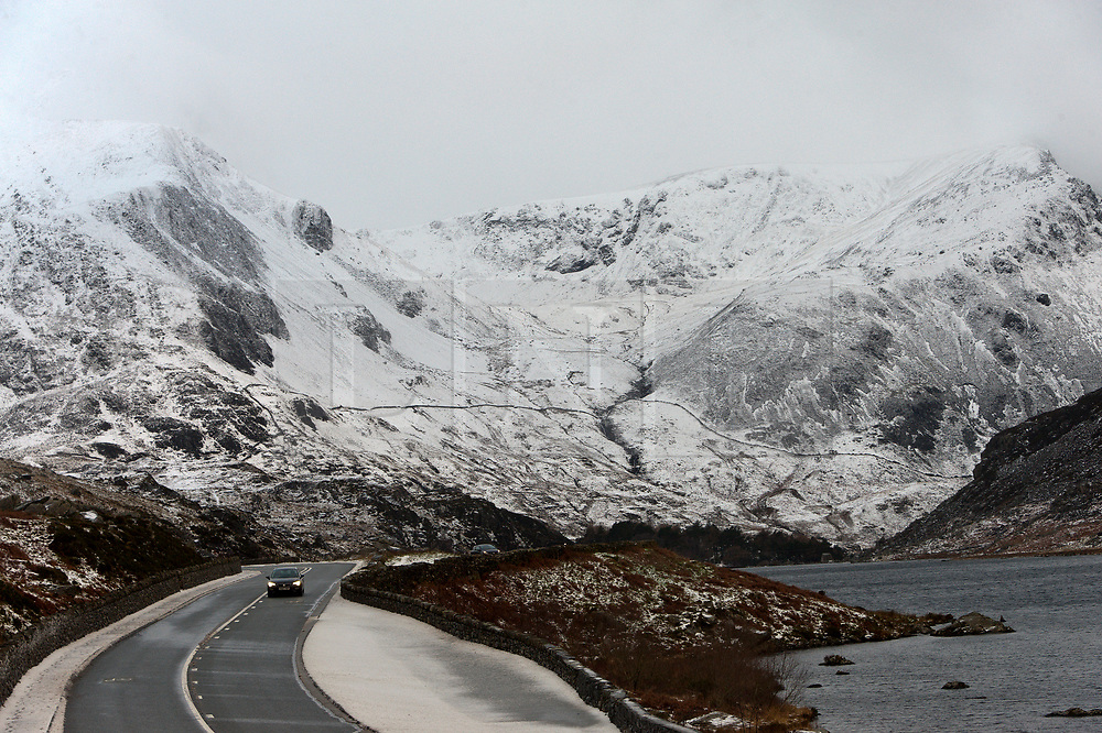 © Licensed to London News Pictures. 22/01/2019. Snowdonia, Gwynedd, Wales, UK. A motorist drives through a bleak wintry landscape along the A5 road near Llyn Ogwen (Lake Ogwen)  in Snowdonia National Park, Gwynedd, Wales, UK. credit: Graham M. Lawrence/LNP