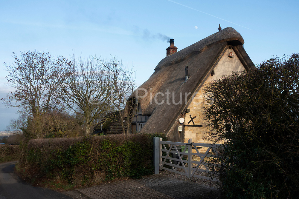Smoke coming from the chimney of a thatched roof cottage near Bredon Hill, England, United Kingdom. Bredon Hill is a hill in Worcestershire, England, south-west of Evesham in the Vale of Evesham. The hill is geologically part of the Cotswolds and lies within the Cotswolds Area of Outstanding Natural Beauty. However, as the result of erosion over millions of years, it now stands isolated in the Vale of Evesham.