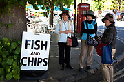 Japanese tourists by a fish and chips sign at Bourton-on-the-Water in The Cotswolds, Gloucestershire, UK.  It is known as the 'Venice of the Cotswolds' because of the bridge-spanned stream that runs through the village, this is one of the most popular places to visit in the area. Popular with both the English themselves and international visitors from all over the world, the area is well known for gentle hillsides 'wolds', outstanding countryside, sleepy ancient limestone villages, historic market towns and for being so 'typically English' where time has stood still for over 300 years. Throughout the Cotswolds stone features in buildings and stone walls act as a common thread in seamlessly blending the historic towns & villages with their surrounding landscape. One of the most 'quintessentially English' and unspoiled regions of England.