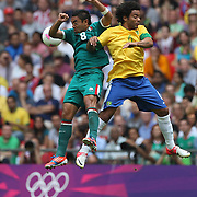 Marco Fabian, Mexico, (left) and Marcelo, Brazil, challenge for the ball during the Brazil V Mexico Gold Medal Men's Football match at Wembley Stadium during the London 2012 Olympic games. London, UK. 11th August 2012. Photo Tim Clayton
