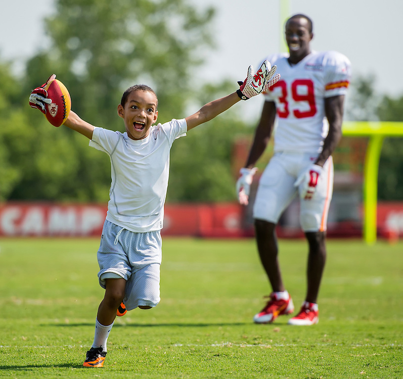Jalaal Abdullah, 7, reacted after catching a pass from his father, Kansas City Chiefs defensive back Husain Abdullah (39), following practice on Monday morning at Kansas City Chiefs summer training camp practice at Missouri Western State University in St. Joseph, Mo.