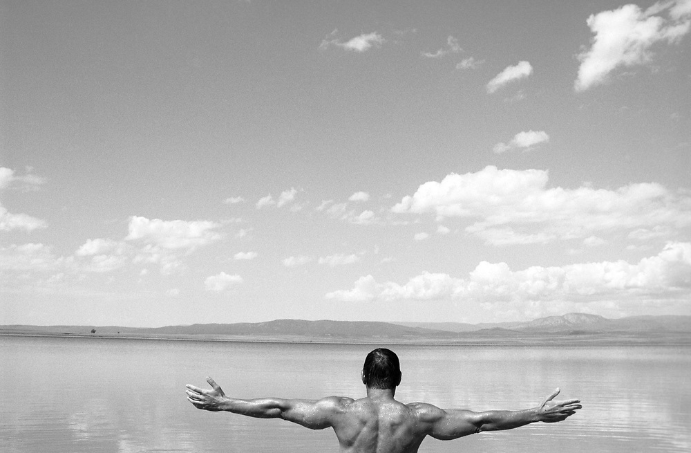rear view of man with arms open facing a lake and mountains in New Mexico