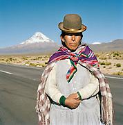 A Woman in traditional dress with Nevado Sajama volcano in background, Tomarapi, Sajama National Park, Oruro, Bolivia