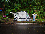 26 JANUARY 2018 - SANTO DOMINGO, ALBAY, PHILIPPINES: People evacuated from the slopes of the Mayon volcano with their old Shelter Box tent on the side of the Legazpi - Tabaco Road, which runs through Santo Domingo. The volcano was relatively quiet Friday, but the number of evacuees swelled to nearly 80,000 as people left the side of  the volcano in search of safety. There are nearly 12,000 evacuees in Santo Domingo, one of the communities most impacted by the volcano. The number of evacuees is impacting the availability of shelter space. Many people in Santo Domingo, on the north side of the volcano, are sleeping in huts made from bamboo and plastic sheeting. The Philippines is now preparing to house the volcano evacuees for up to three months.       PHOTO BY JACK KURTZ