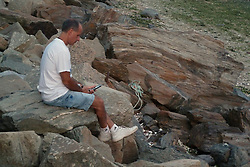 Reading his device, along the Shoreline at Twilight. Gathering of the Vibes 2010, Seaside Park, Bridgeport, Connecticut