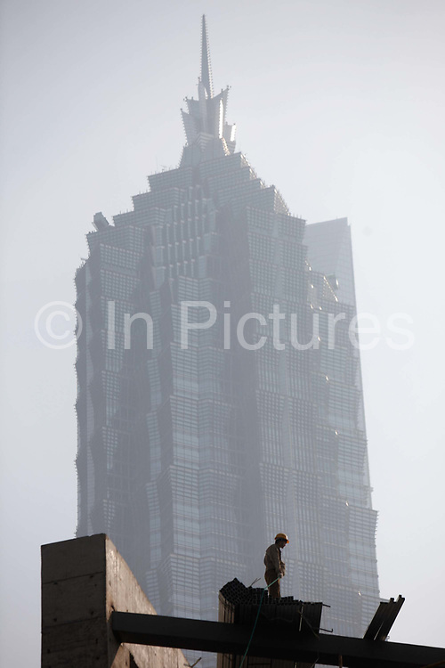 Construction workers operate on a scaffolding in front of the Jin Mao Grand Hyatt in Shanghai, China on 18 December, 2009. Shanghai is on its way of becoming one of the world's most important financial centers.