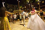 "The Mai Tai bar at the historic Royal Hawaiian Hotel, also known as the ""Pink Lady"". Japanese newlyweds learning Hula."