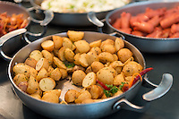 Skillet with saute potatoes in a breakfast buffet.