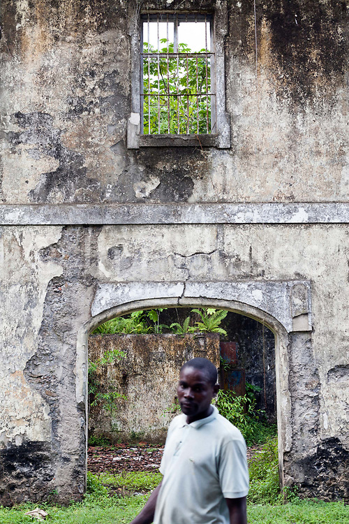A man stands before an abandoned Colonial Roca near Praia Micondo, Sao Tome. Sao Tome and Principe. Sao Tome and Principe, are two islands of volcanic origin lying off the coast of Africa. Settled by Portuguese convicts in the late 1400s and later a centre for slaving, their independence movement culminated in a peaceful transition to self government from Portugal in 1975.