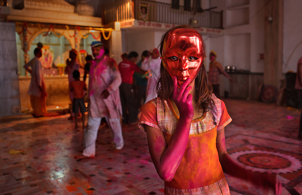 Bathed in colored powder and a red mask, a young girl celebrates India's spring festival of Holi, also known as the Festival of Colors.