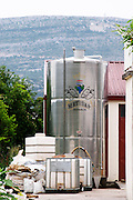 A new stainless steel fermentation tank outside with the Matusko symbol. Matusko Winery. Potomje village, Dingac wine region, Peljesac peninsula. Matusko Winery. Dingac village and region. Peljesac peninsula. Dalmatian Coast, Croatia, Europe.