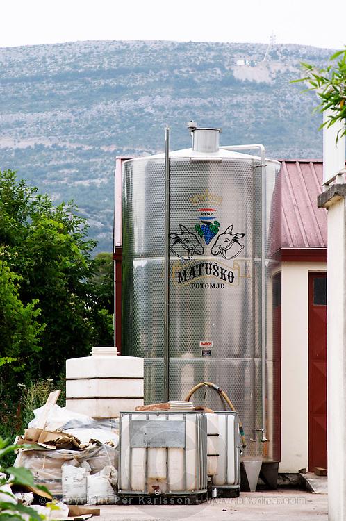 A new stainless steel fermentation tank outside with the Matusko symbol. Matusko Winery. Potomje village, Dingac wine region, Peljesac peninsula. Matusko Winery. Dingac village and region. Peljesac peninsula. Dalmatian Coast, Croatia, Europe.