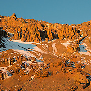 The setting sun casts a golden light on the rugged and steep Western Breach as seen from Arrow Glacier Camp on Mt Kilimanjaro's Lemosho Route.