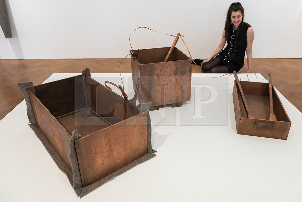 """© Licensed to London News Pictures. 17/04/2018. LONDON, UK. A staff member views """"Kleines Kraftwerk (Small Power Station)"""", 1984, copper, iron and felt, at the preview of """"Joseph Beuys: Utopia at the Stag Monuments"""", at the Galerie Thaddaeus Ropac in Dover Street.  The retrospective is the most important UK exhibition of Beuys' work in over a decade, presenting major sculptures and rarely seen works from 1947 to 1985, and runs from 18 April to 16 June.  Photo credit: Stephen Chung/LNP"""