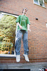Teenage boy with Autism jumping,
