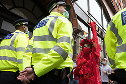 London, UK. 23rd August, 2021. A member of the Extinction Rebellion Red Rebel Brigade raises a clenched fist in front of a Metropolitan Police officer during the first day of Impossible Rebellion protests in the Covent Garden area. Extinction Rebellion are calling on the UK government to cease all new fossil fuel investment with immediate effect. Credit: Mark Kerrison/Alamy Live News