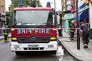 A London Fire Brigade unit responding to an emergency on Church Street, Stoke Newington, London, United Kingdom.  Firefighters have seal off the area with barricade tape to ensure public safety while they work.
