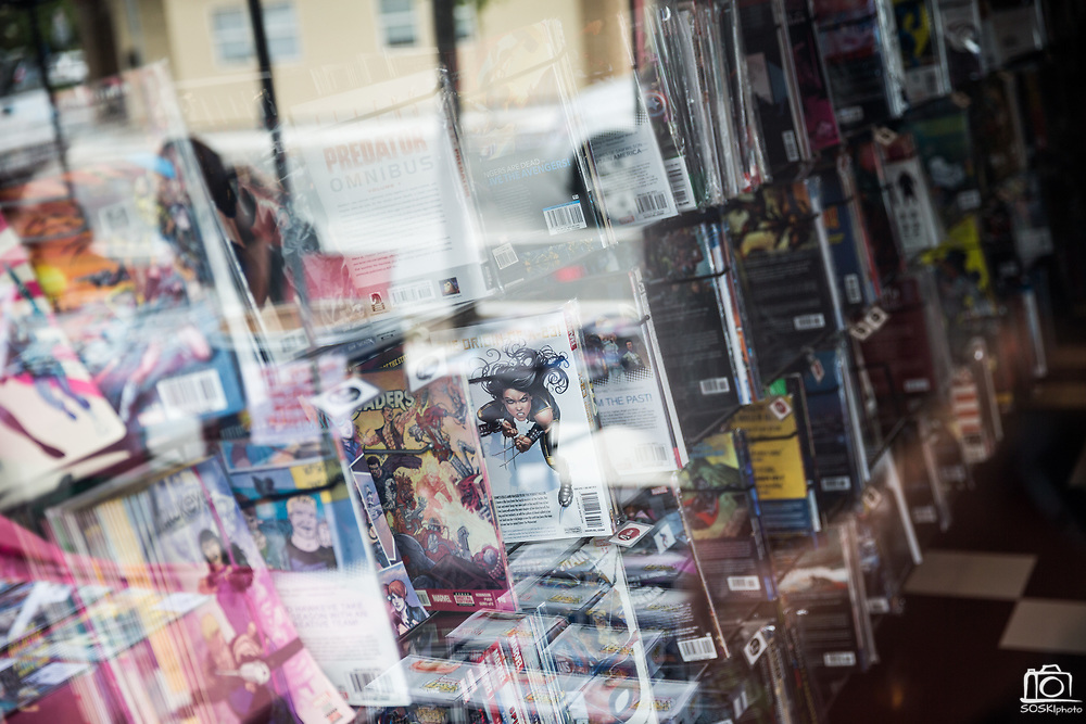 Walls of new comics books are seen throw a window during Free Comic Book Day at Black Cat Comics in Milpitas, California, on May 6, 2017. (Stan Olszewski/SOSKIphoto)