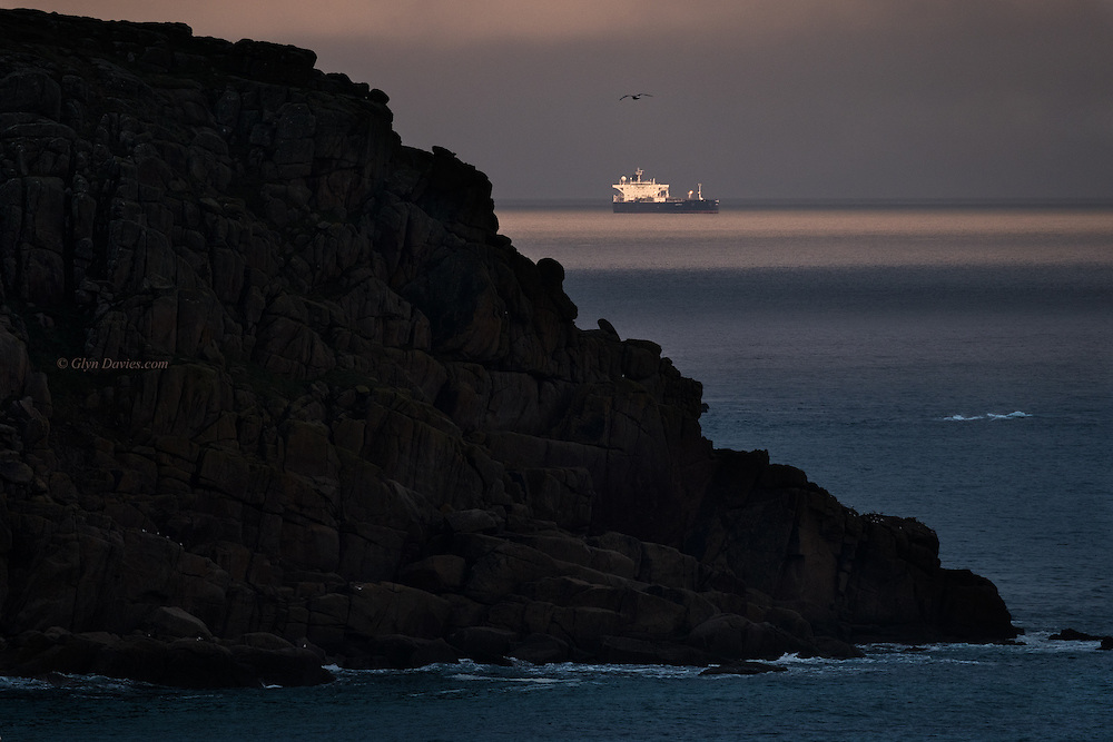 A ship at dusk at anchor off Mount's Bay in Cornwall. The whole landscape was dark and rather ominous looking in the heavy weather but the large ship was temporarily illuminated by a last pulse of light before the clouds closed over for the night.