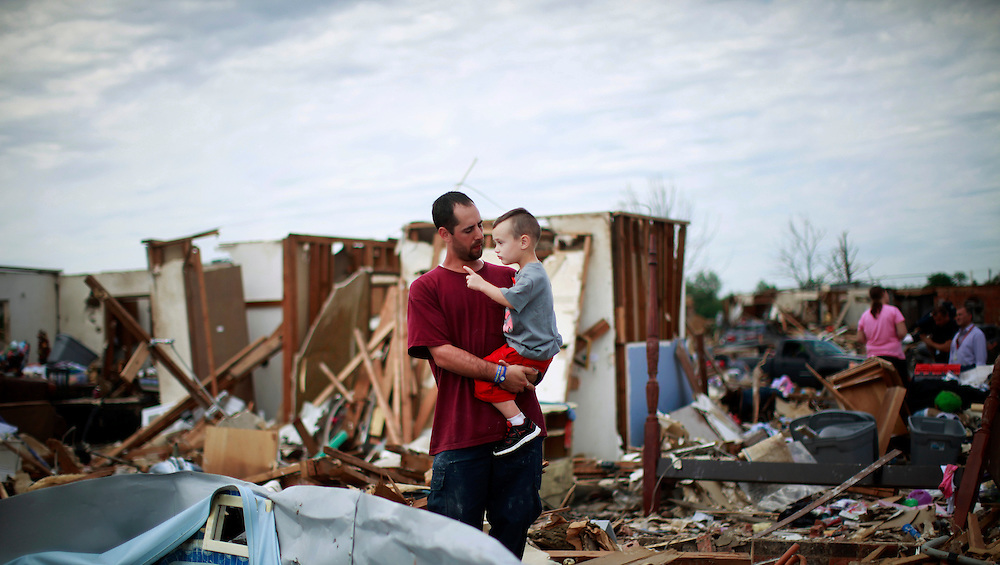 Justin Stephan (L) shows his son Timothy, 3, his tornado-destroyed home for the first time since the storm on 6th Avenue in Moore, Oklahoma May 23, 2013. The tornado was the strongest in the United States in nearly two years and cut a path of destruction 17 miles long and 1.3 miles wide. REUTERS/Rick Wilking (UNITED STATES)
