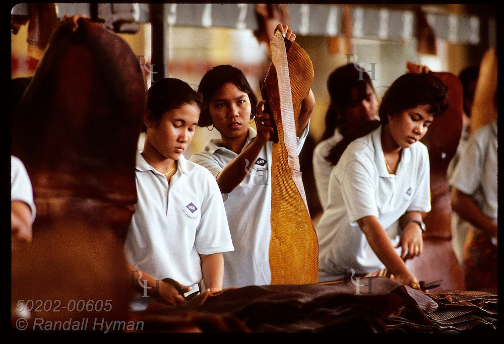 Women armed with scissors inspect rubber mats to cut out any impurities before export; Krabi. Thailand