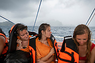 Three friends from Belgium huddle in a chilling rain during a day tour on a traditional bangka boat of the Bacuit Archipelago around El Nido, Palawan, Philippines. (July 14, 2019)