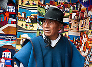 A man sells rugs in Otavalo, Ecuador, South America. The culturally vibrant town of Otavalo attracts many tourists to a valley of the Imbabura Province of Ecuador, surrounded by the peaks of Imbabura 4,610m, Cotacachi 4,995m, and Mojanda volcanoes. The indigenous Otavaleños are famous for weaving textiles, usually made of wool, which are sold at the famous Saturday market and smaller markets during the rest of the week. The Plaza del Ponchos and many shops tantalize buyers with a wide array of handicrafts. Nearby villages and towns are also famous for particular crafts: Cotacachi, the center of Ecuador's leather industry, is known for its polished calf skins; and San Antonio specializes in wood carving of statues, picture frames and furniture. Otavaliña women traditionally wear distinctive white embroidered blouses, with flared lace sleeves, and black or dark over skirts, with cream or white under skirts. Long hair is tied back with a 3cm band of woven multi colored material, often matching the band which is wound several times around their waists. They usually have many strings of gold beads around their necks, and matching tightly wound long strings of coral beads around each wrist. Men wear white trousers, and dark blue ponchos. Otavalo is also known for its Inca-influenced traditional music (sometimes known as Andean New Age) and musicians who travel around the world.