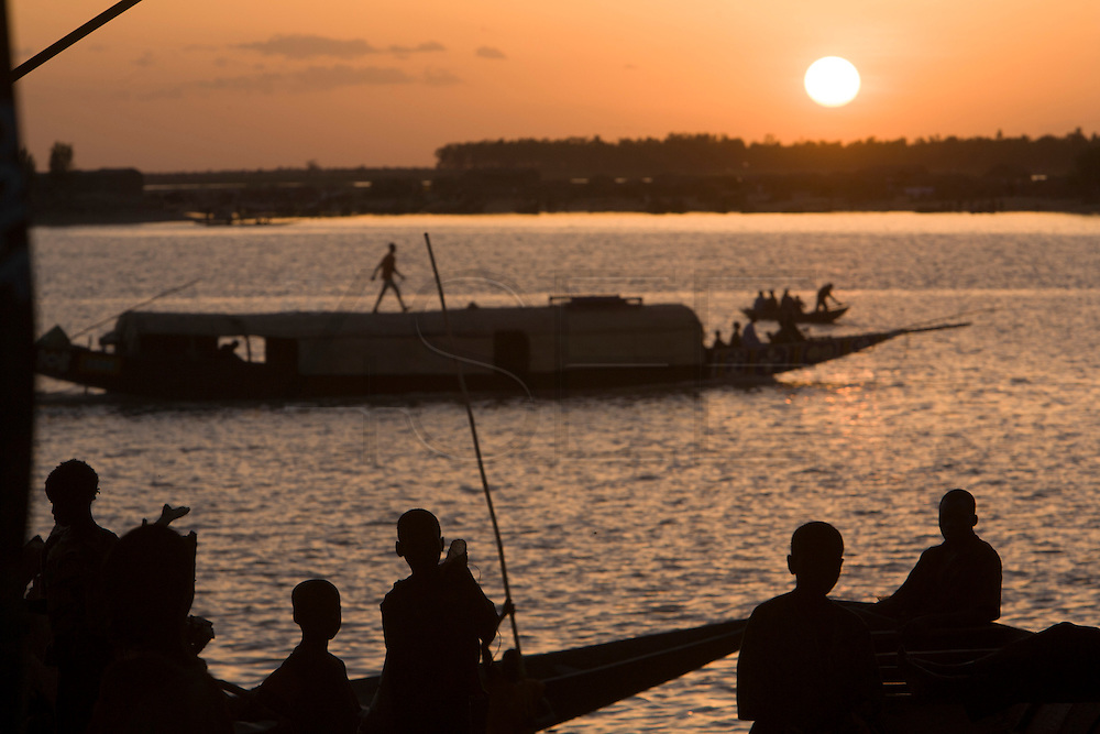 Children watching sunset at the riverside. At the confluence of the Niger and the Bani rivers, between Timbuktu and Ségou, Mopti is the second largest city in Mali, and the hub for commerce and tourism in this west-african landlocked country.