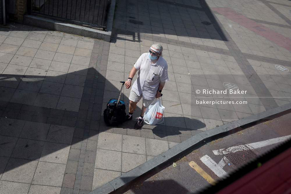 During the UK's Coronavirus pandemic lockdown and on the day when a further 255 deaths occurred, bringing the official covid deaths to 37,048, <br /> a man wearing a face mask plus face shield awaits his bus at a bus stop, on 26th May 2020, in London, England.